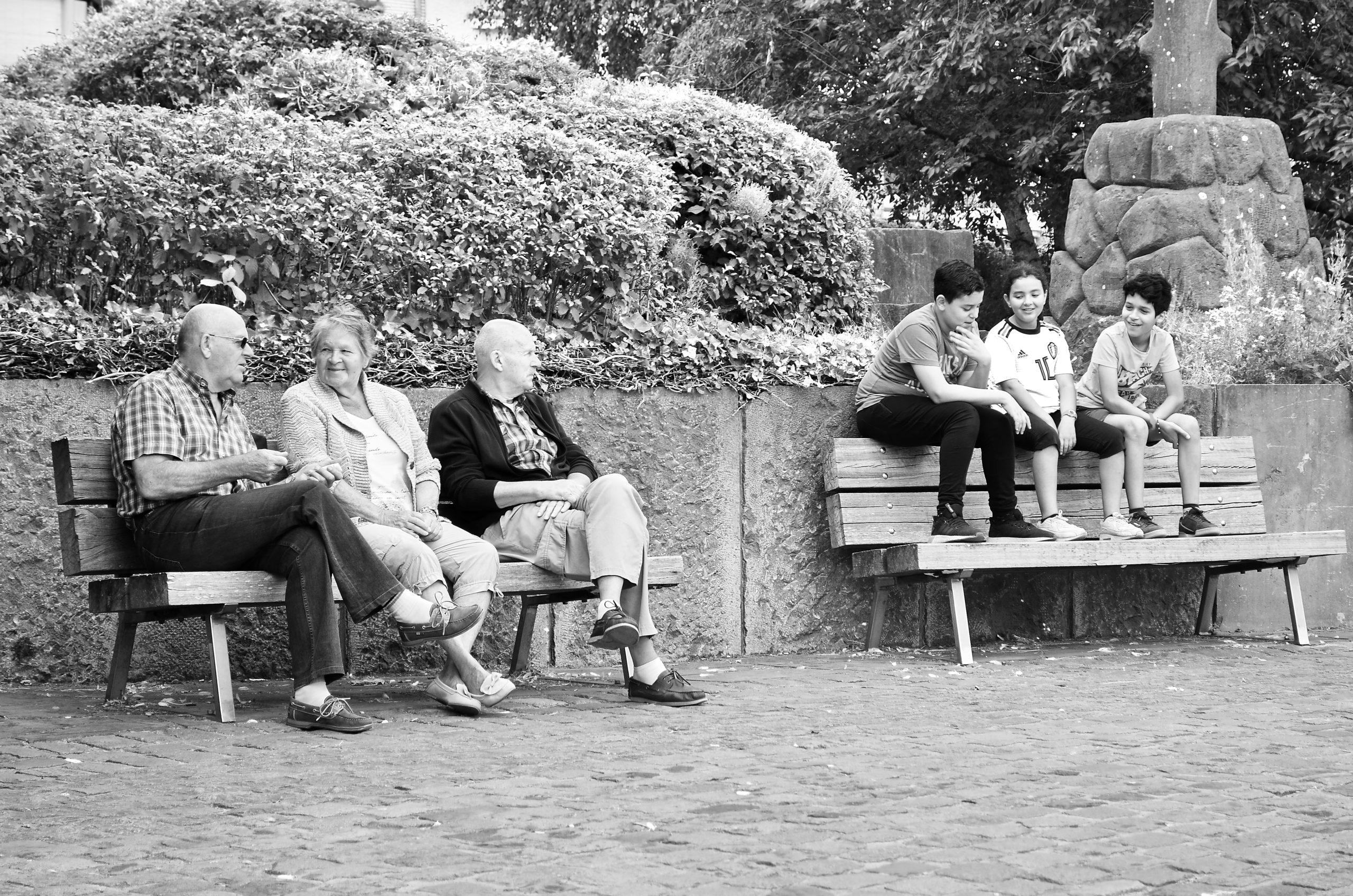 Photo noir et blanc avec 3 personnes agées sur un banc et 3 jeunes sur un autre banc