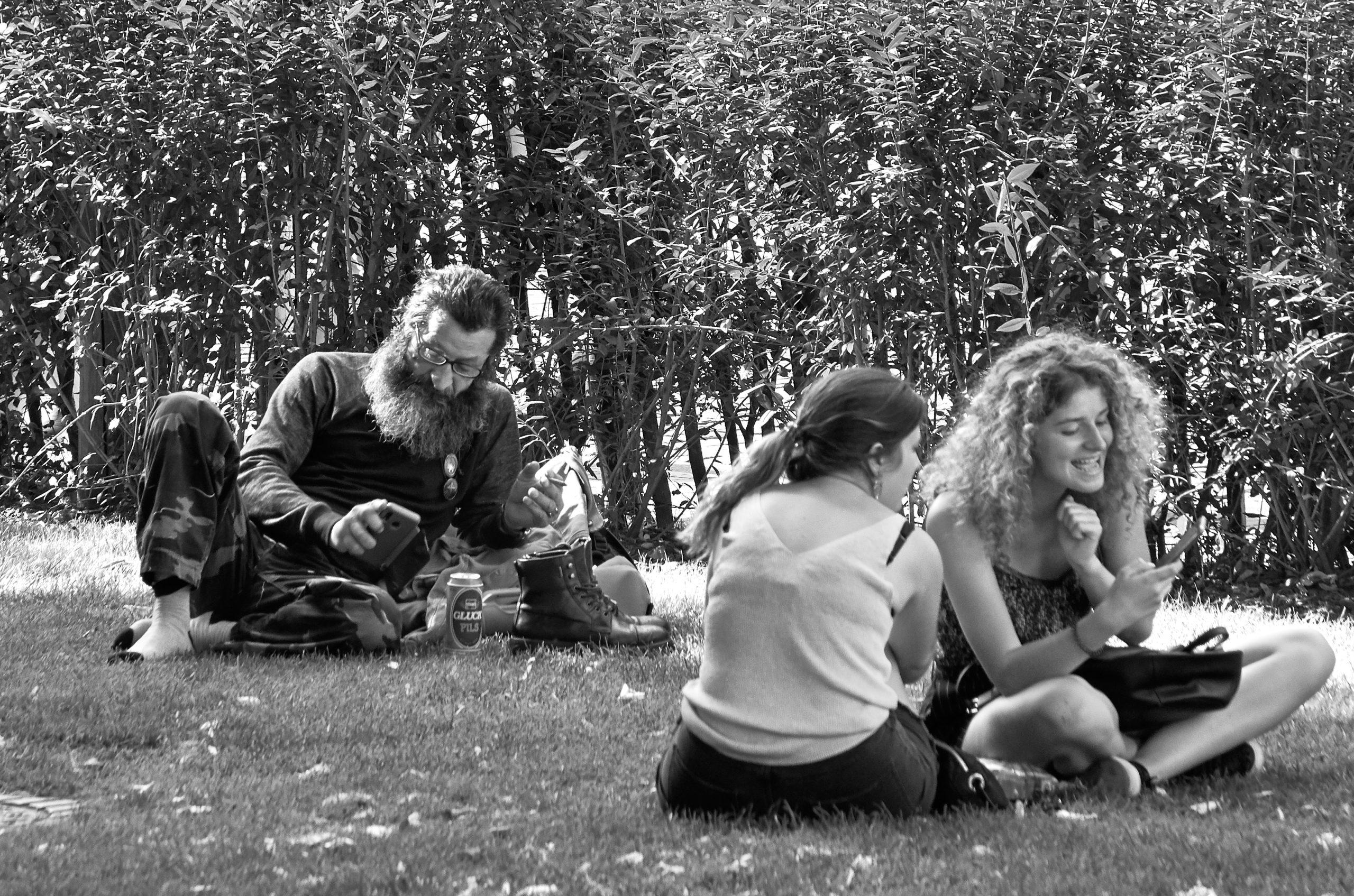Photo noir et blanc d'un homme et deux femmes assises dans l'herbe dans un parc
