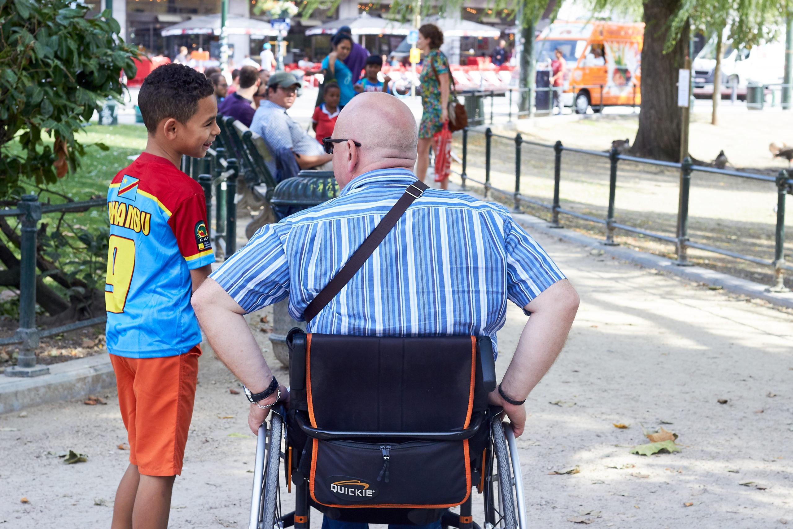Personne à mobilité réduite dans une chaise roulante de dos discutant avec un jeune garçon