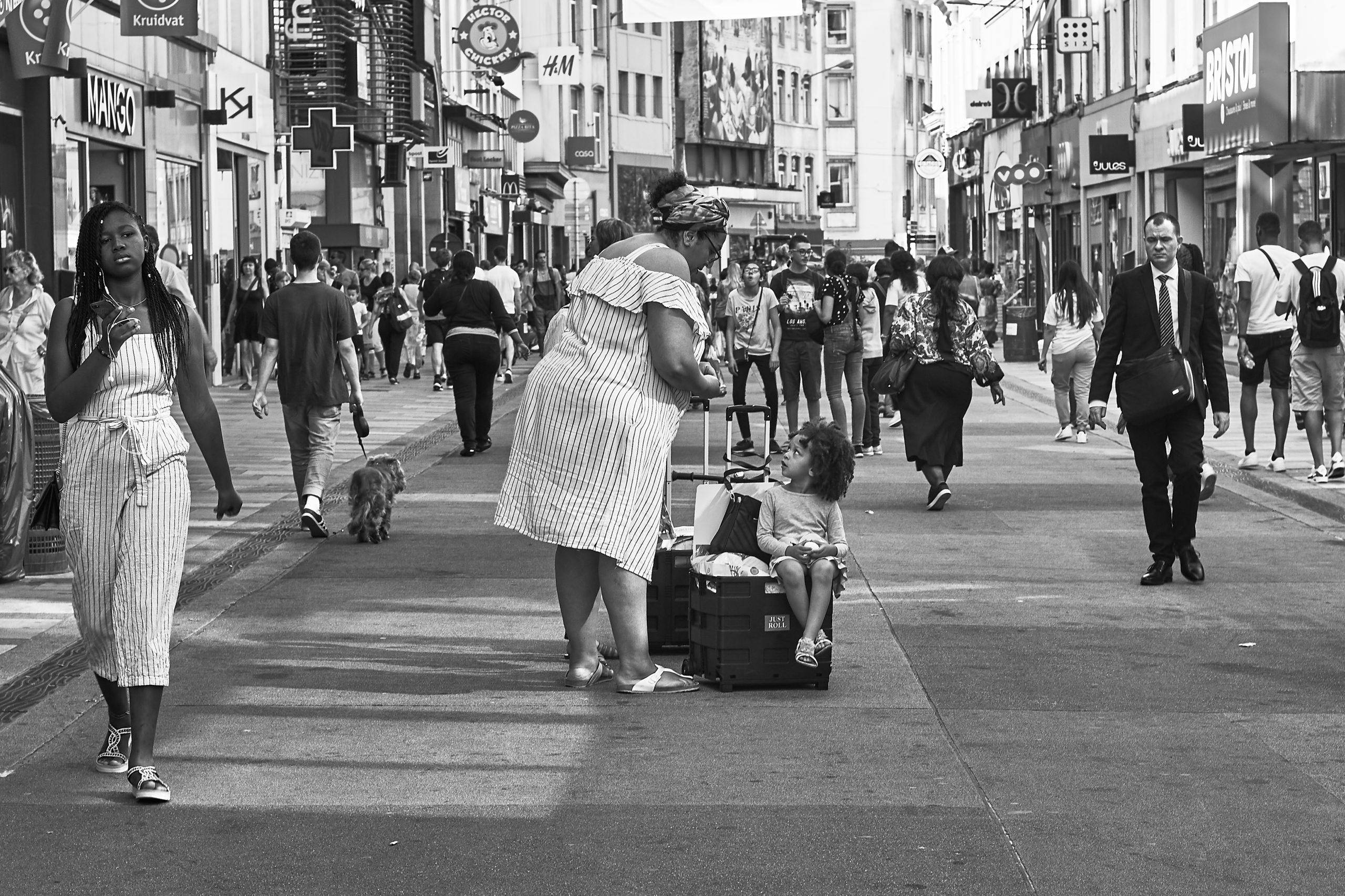 Photo noir et blanc d'une rue dans le centre ville de Bruxelles avec une maman et son enfant ayant fait des courses