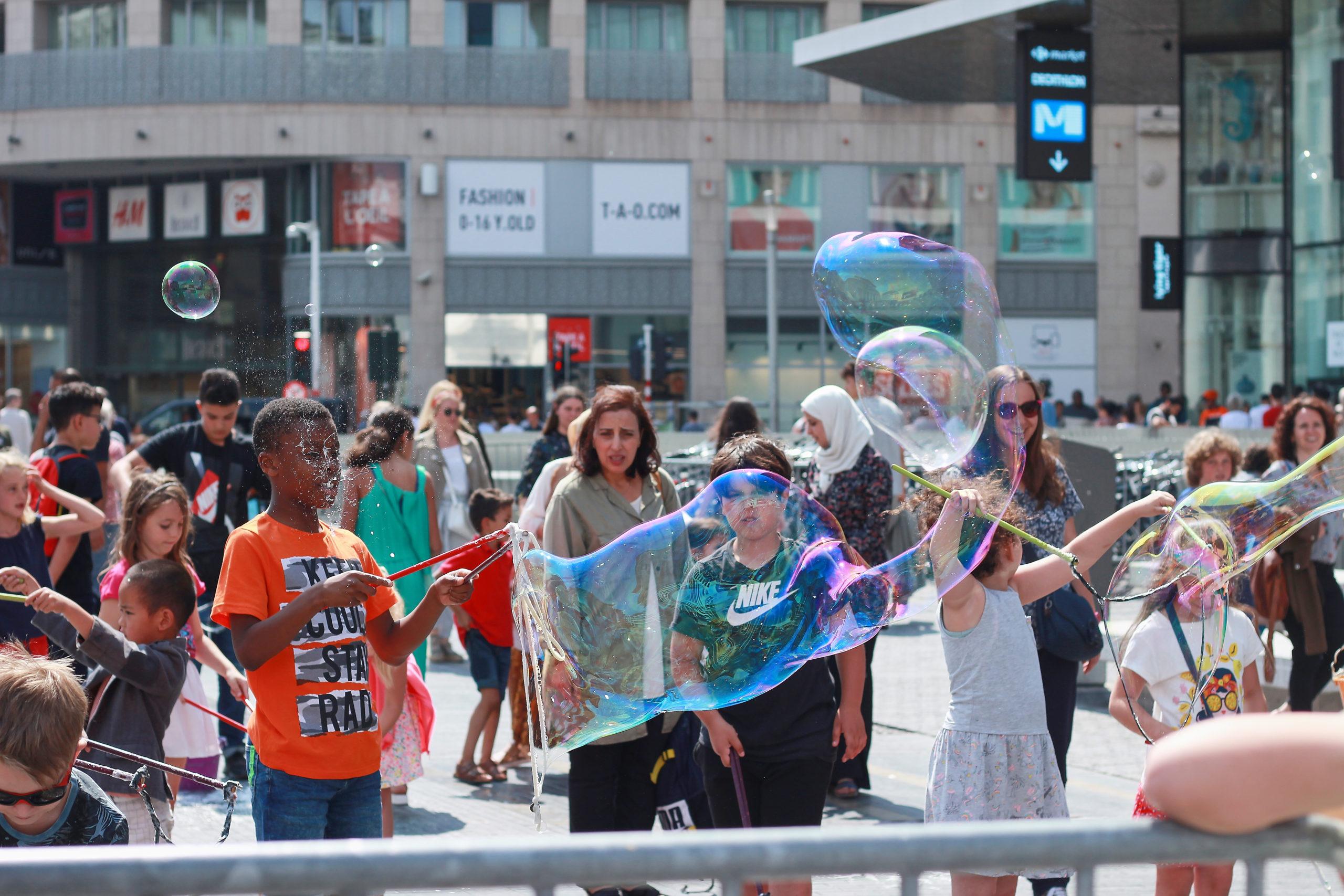 Enfants dans le centre ville de Bruxelles réalisant des bulles de savon XXL