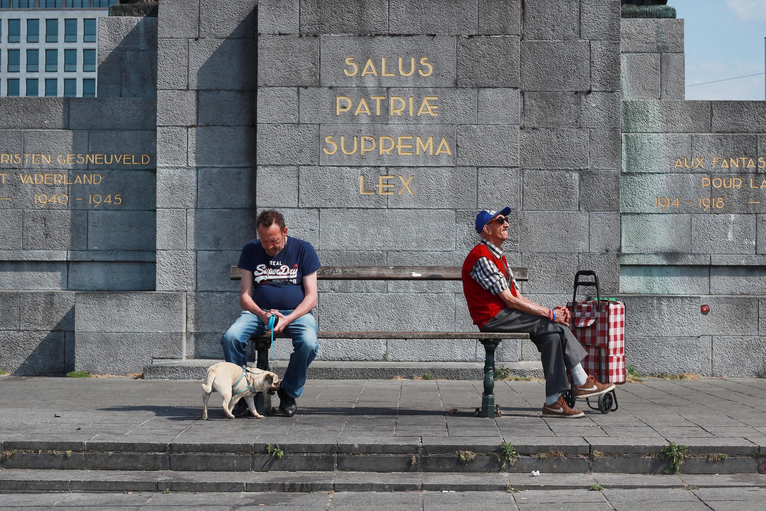 Deux hommes assis chacun à l'extrémité d'un banc et l'un tient un chien en laisse