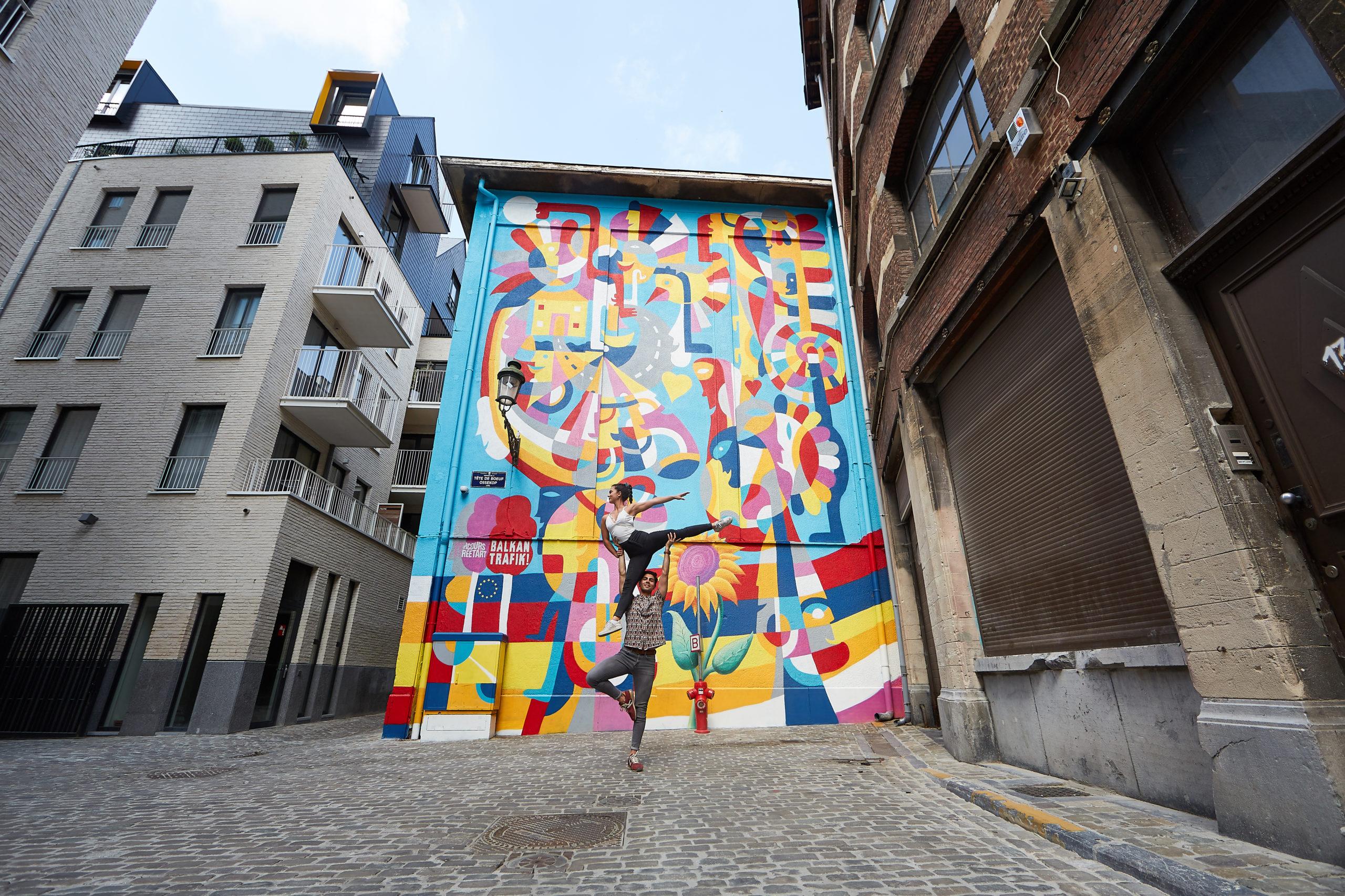 Deux jeunes adolescents effectuant une figure en pleine rue devant un mur très coloré