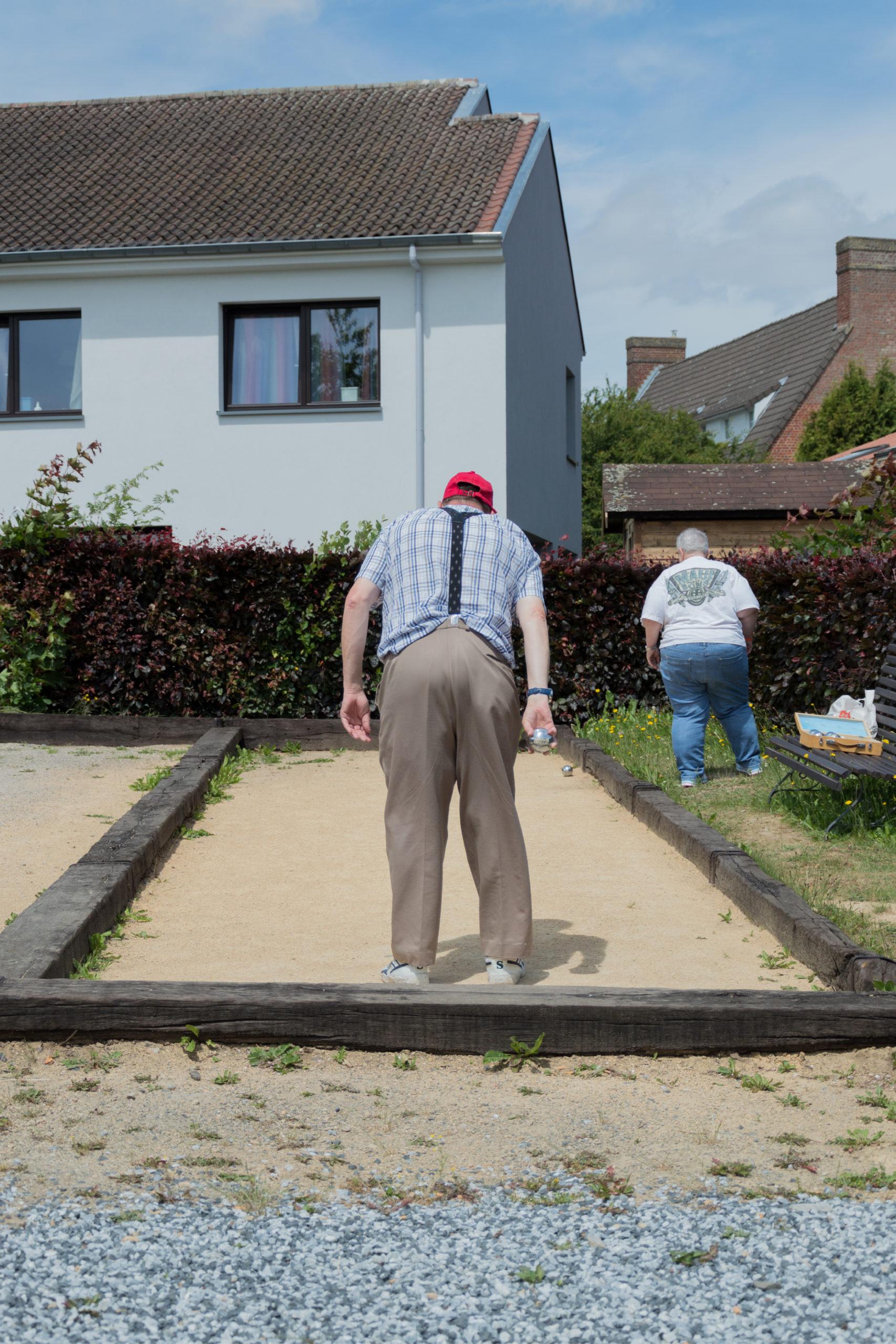 Personne handicapée de dos jouant à la pétanque sur un terrain de pétanque en extérieur