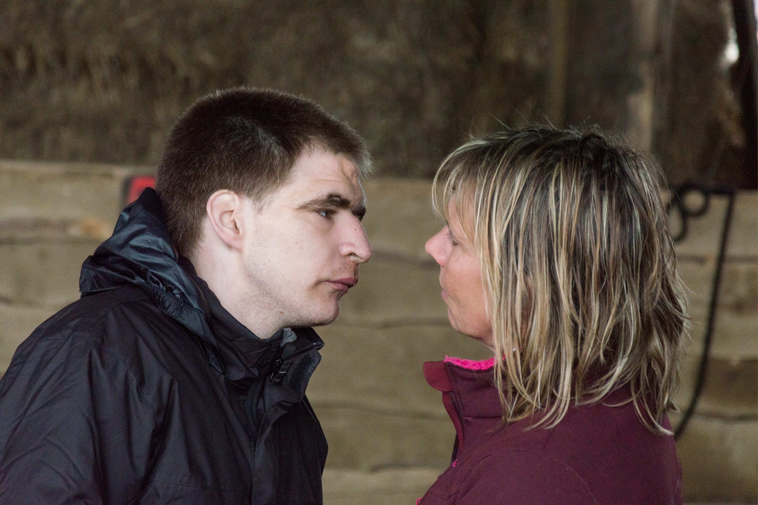Un homme handicapé en manteau noir et une dame en manteau de couleur aubergine se regardant droit dans les yeux