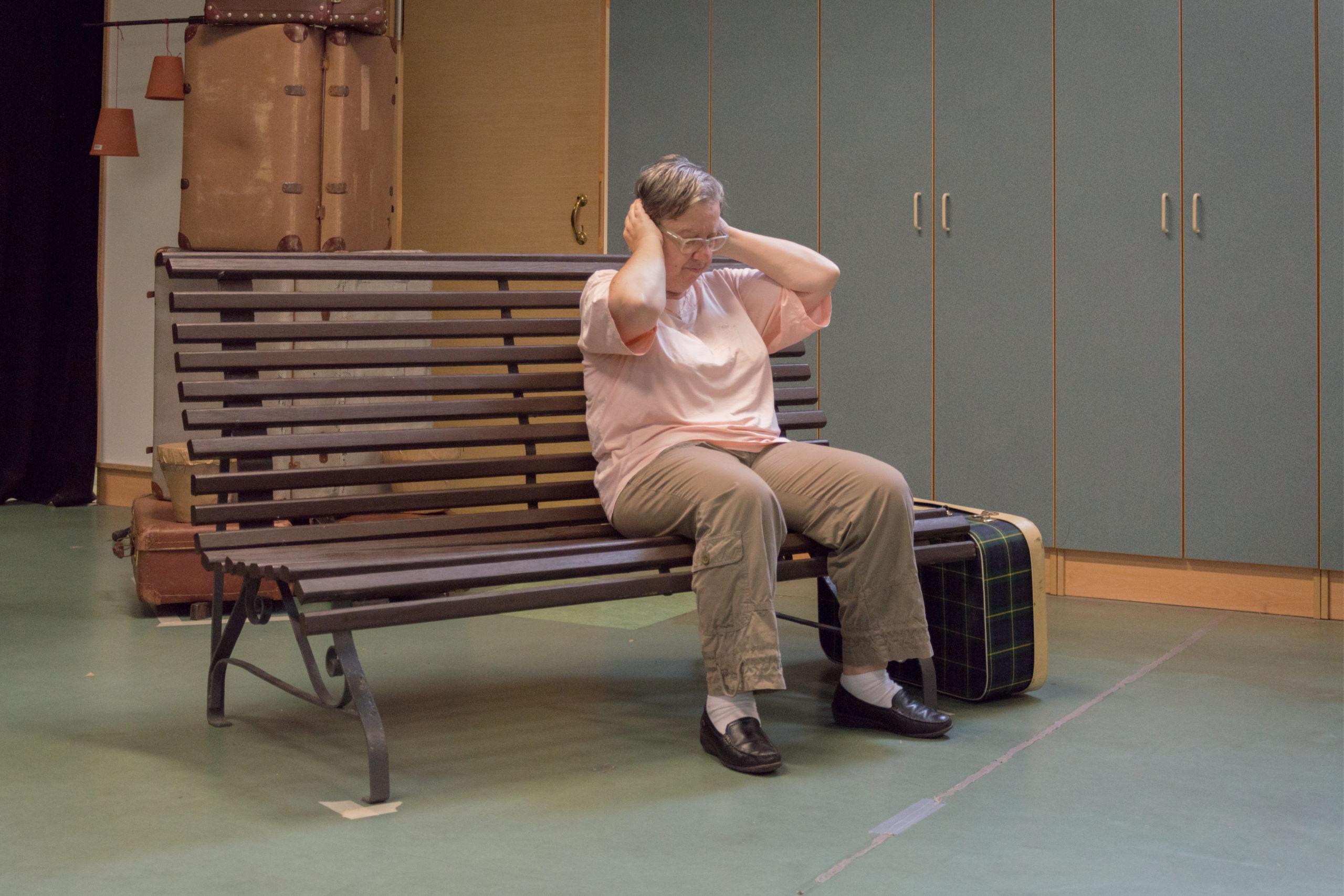 Dame handicapée assise sur un banc se bouchant les oreilles avec ses deux mains