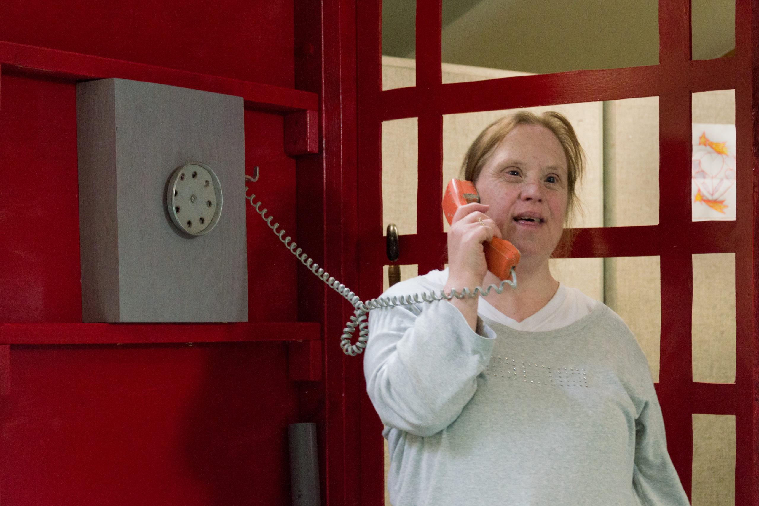 Dame handicapée dans une cabine rouge téléphonique tenant le cornet de téléphone