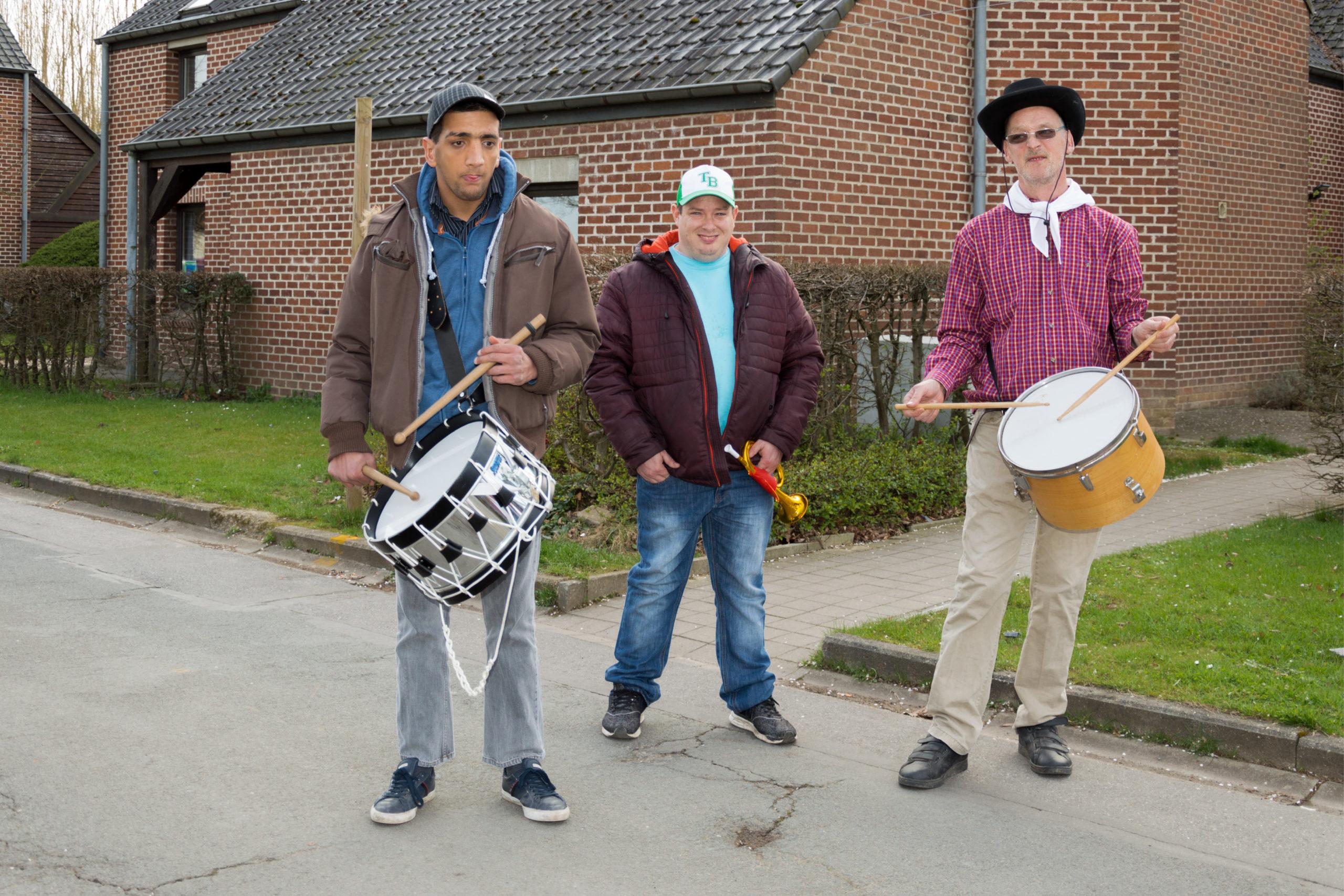 Trois hommes handicapés à l'extérieur dont deux tenant un tambour chacun et le troisième une trompette