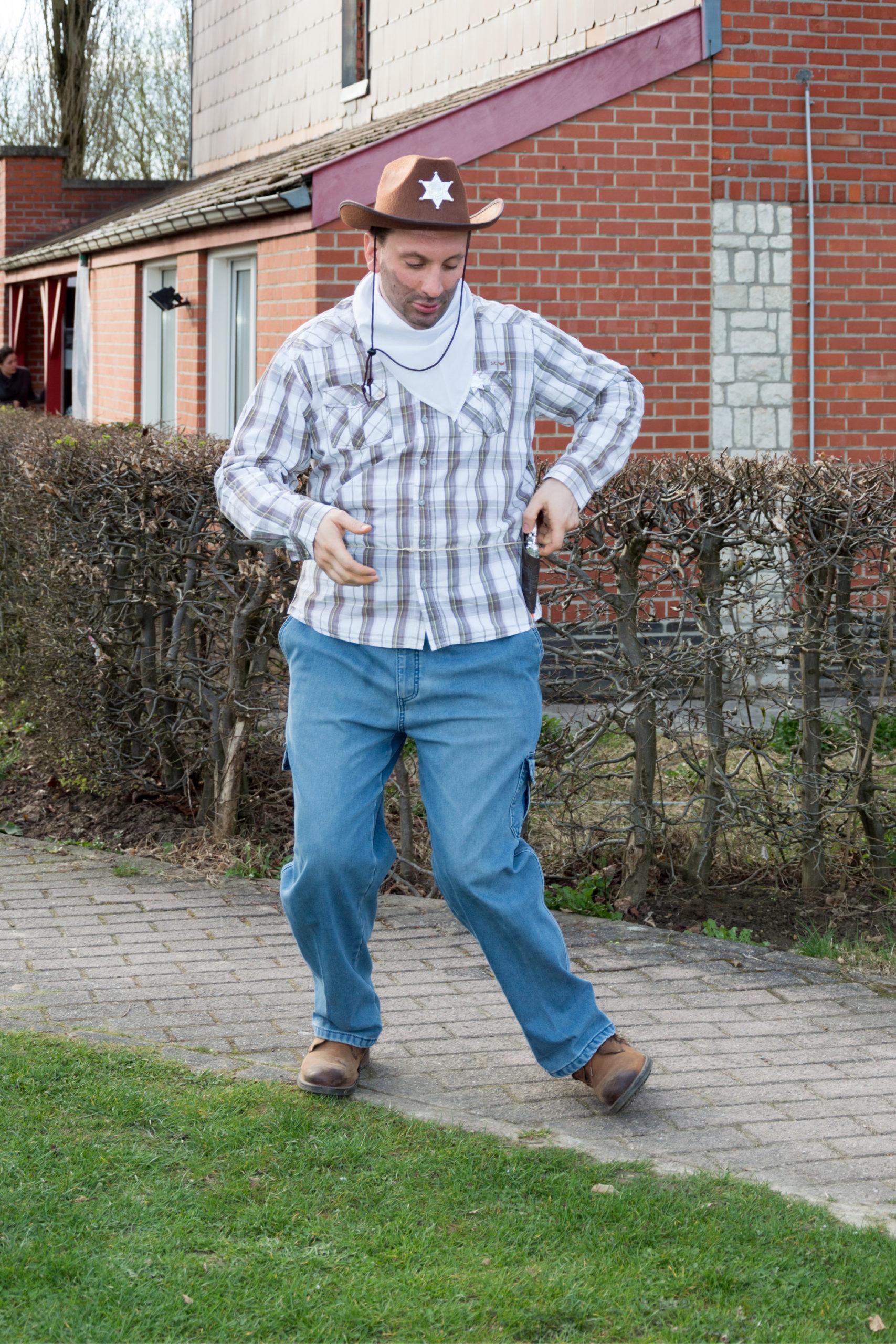Homme handicapé à l'extérieur en tenue de cow-boy prenant son revolver en plastique
