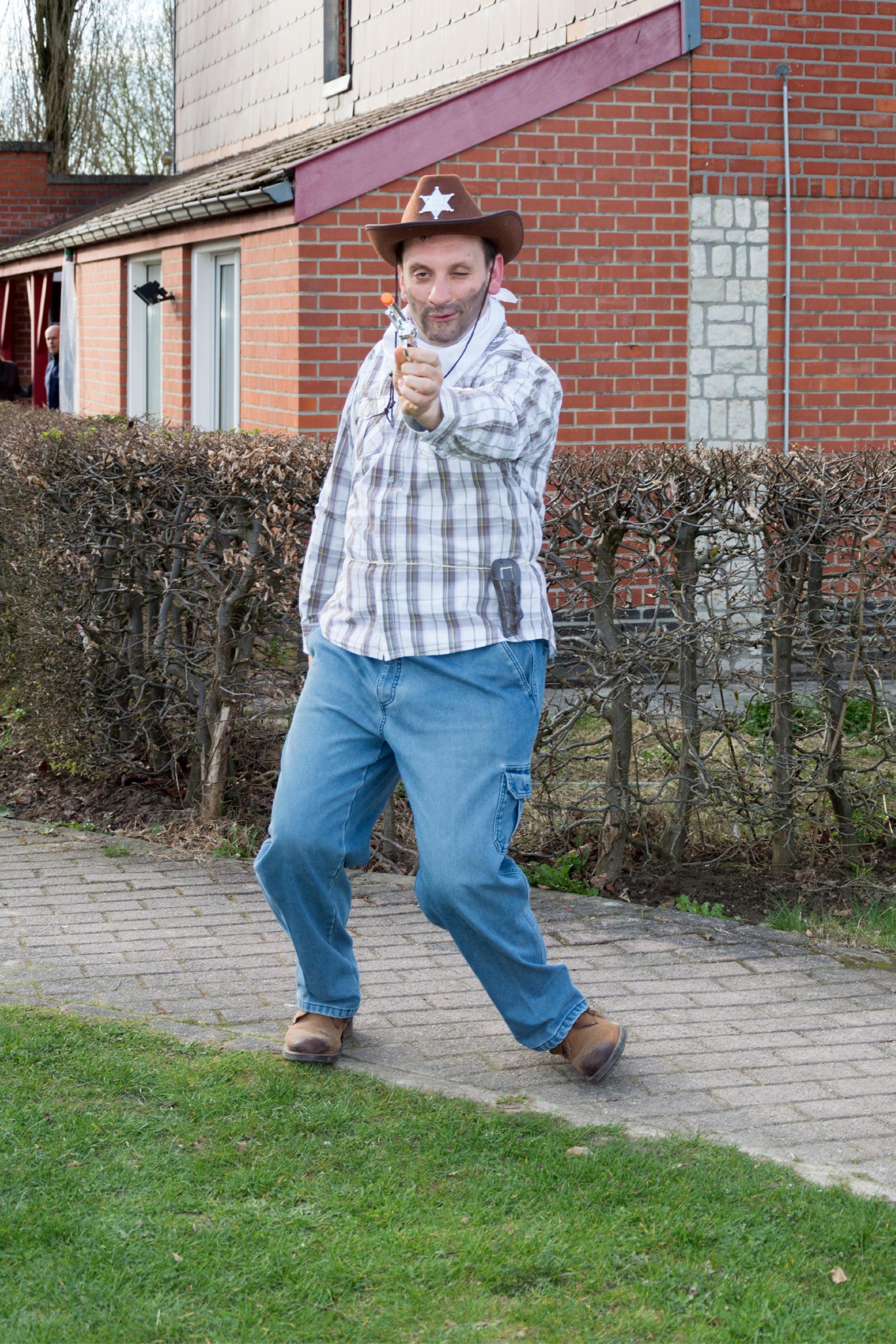 Homme handicapé à l'extérieur en tenue de cow-boy tirant dans notre direction avec son revolver en plastique