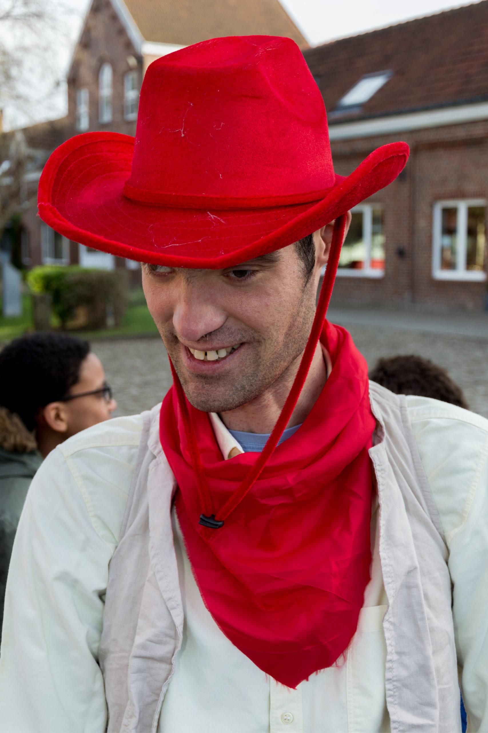 Portrait d'un jeune homme handicapé portant un chapeau et un foulard de cow boy couleur rouge