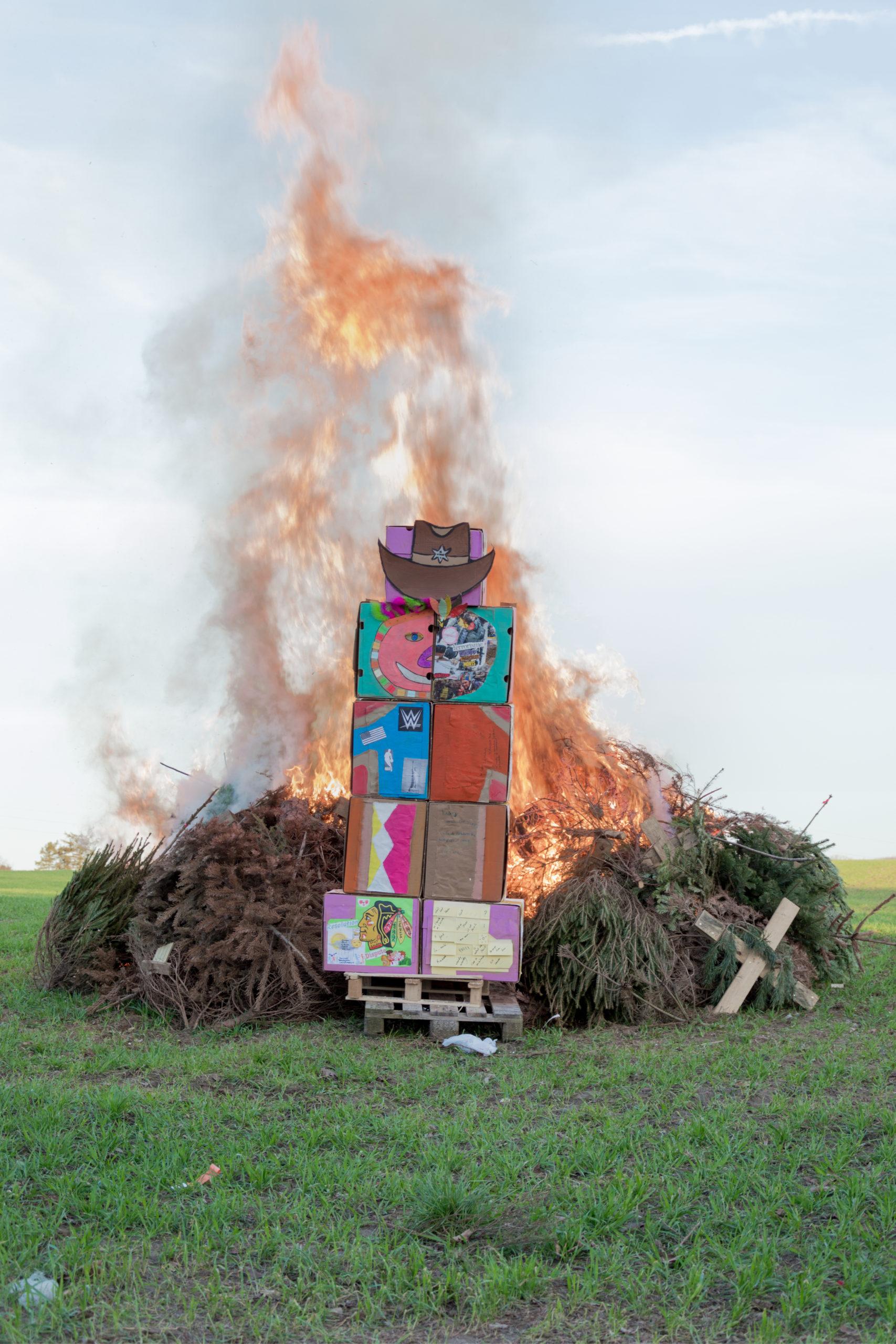 Feu de joie dans un champ avec un totem en carton sur le thème des cow-boys