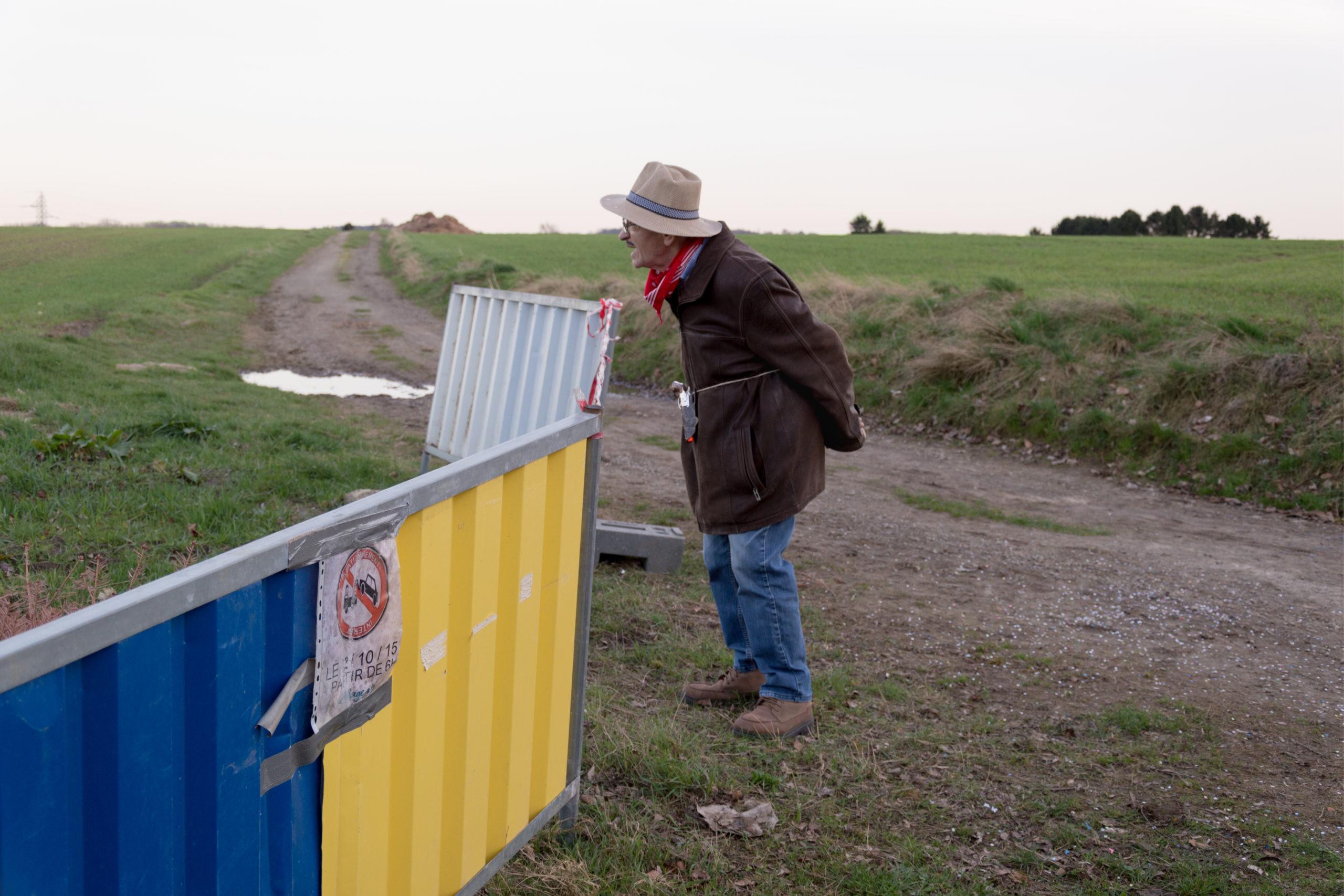 Vieil homme handicapé habillé en cow boy à l'extérieur regardant quelque chose dans un champ