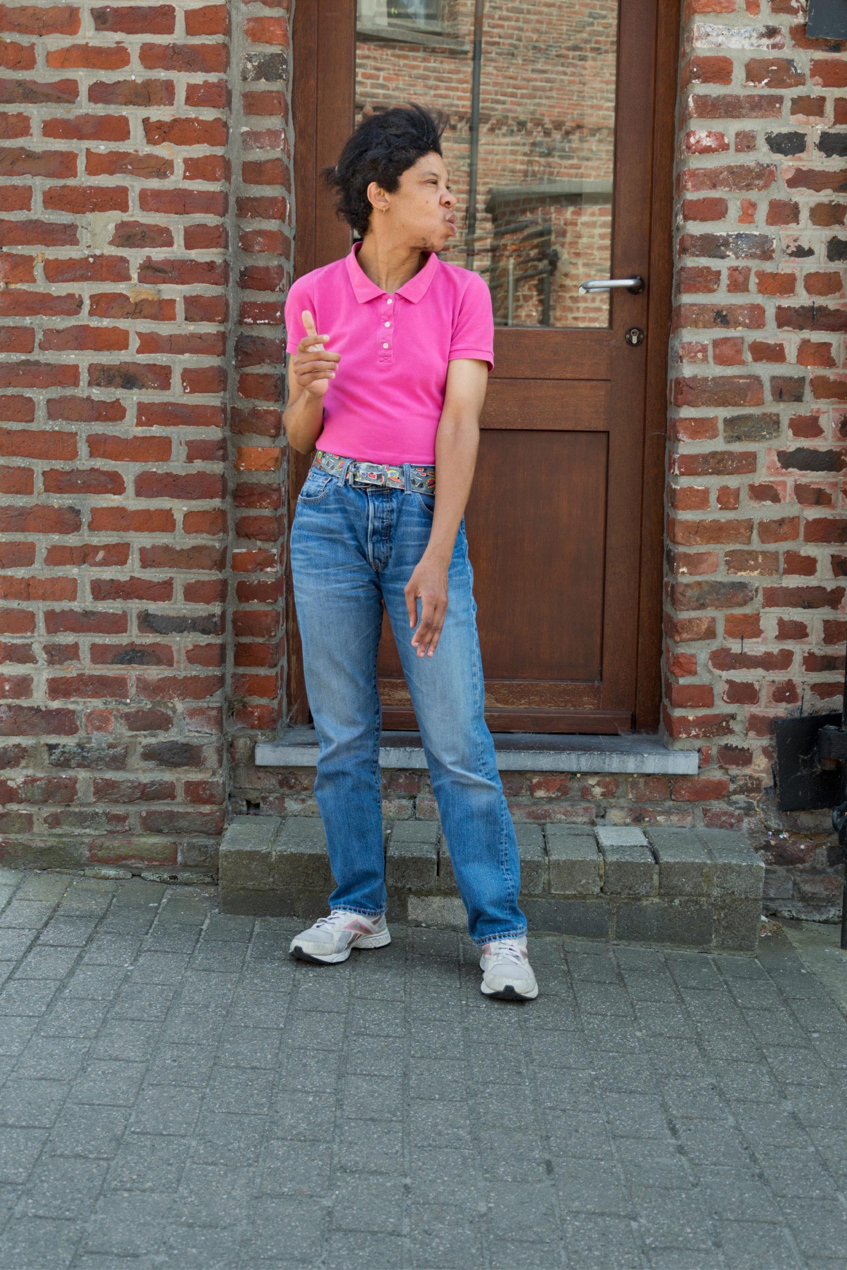 Jeune dame handicapée dehors devant une porte d'entrée d'une maison en brique rouge