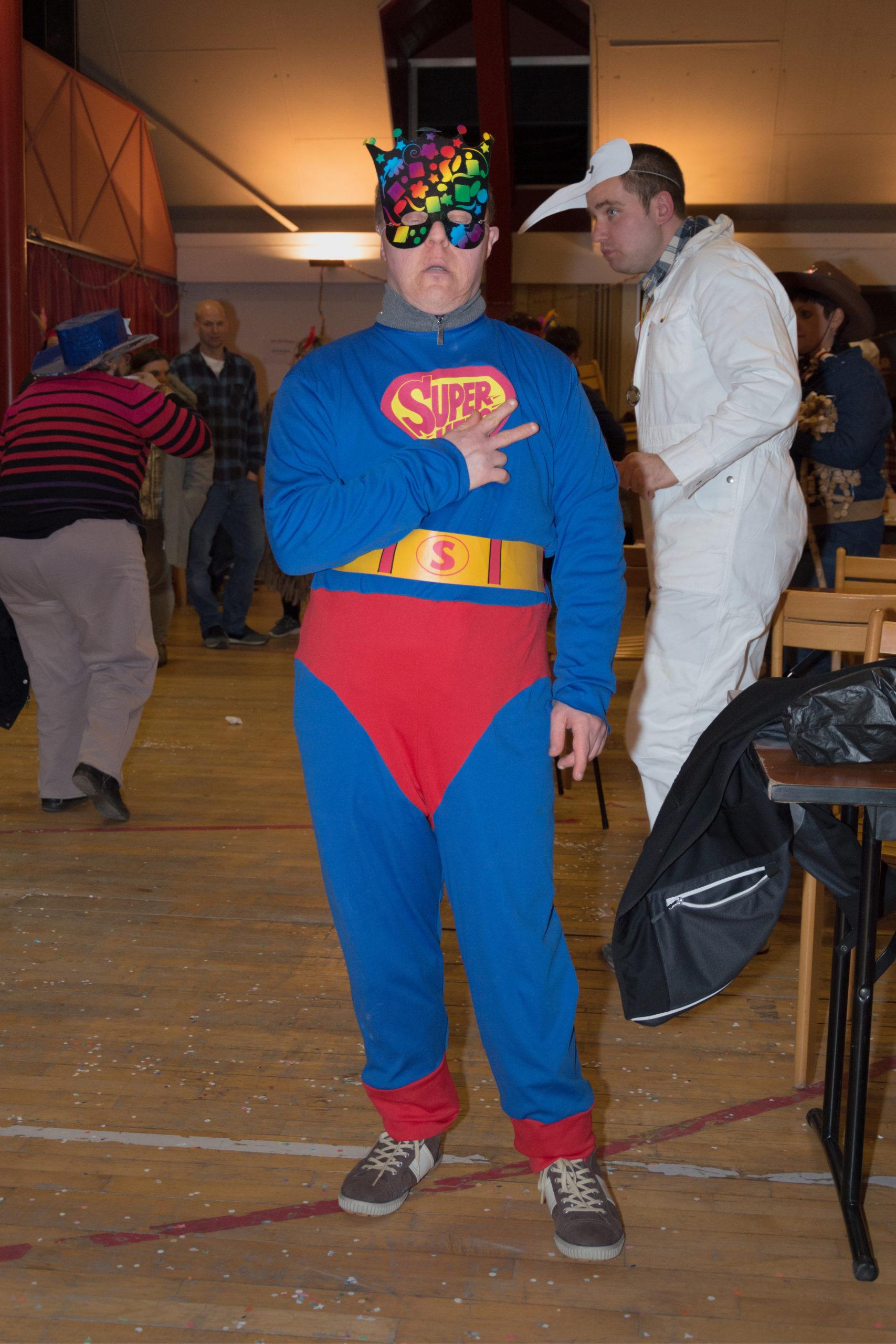Jeune homme handicapé déguisé en Superman et portant un masque multicolor