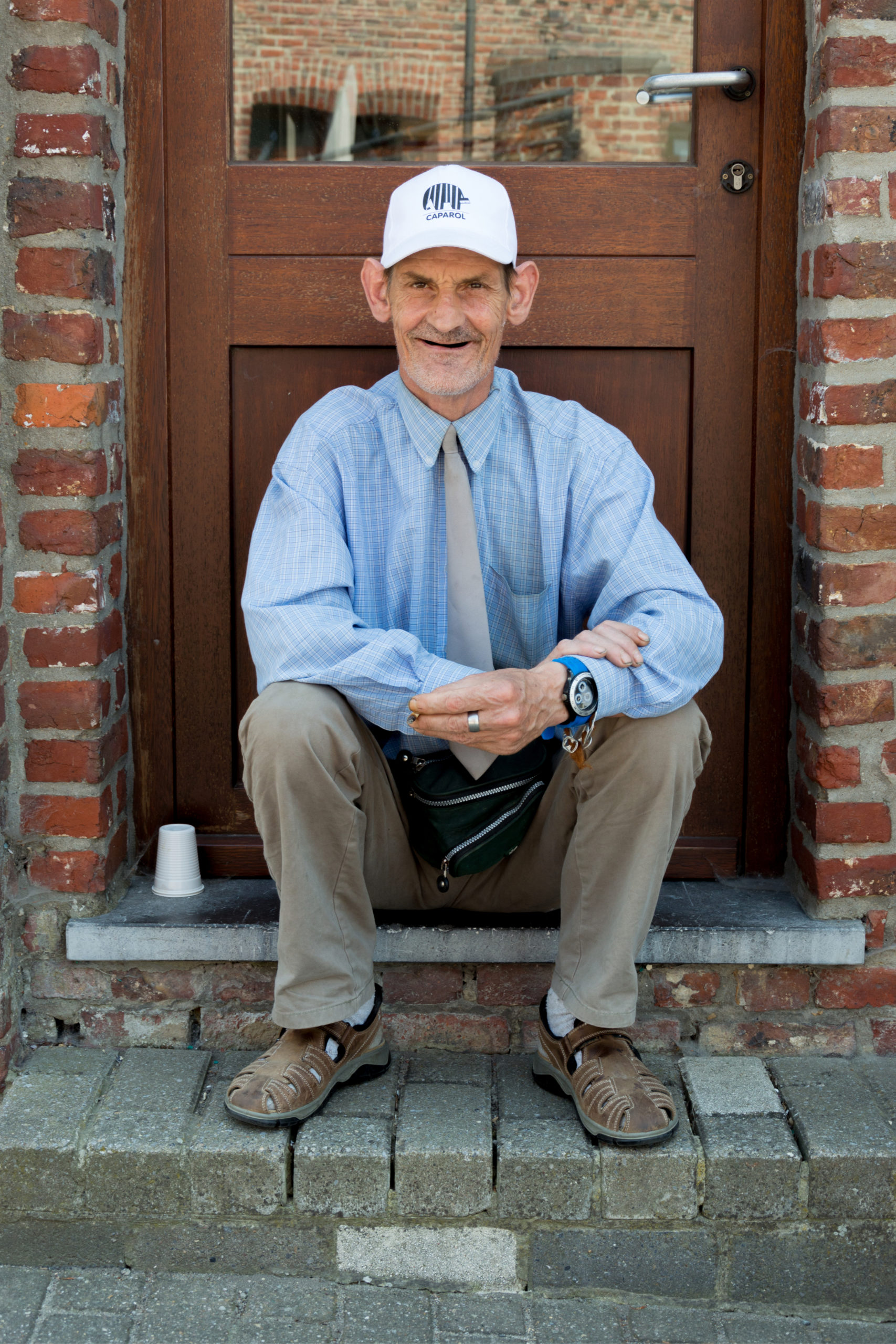 Vieil homme handicapé assis dehors devant une porte en bois