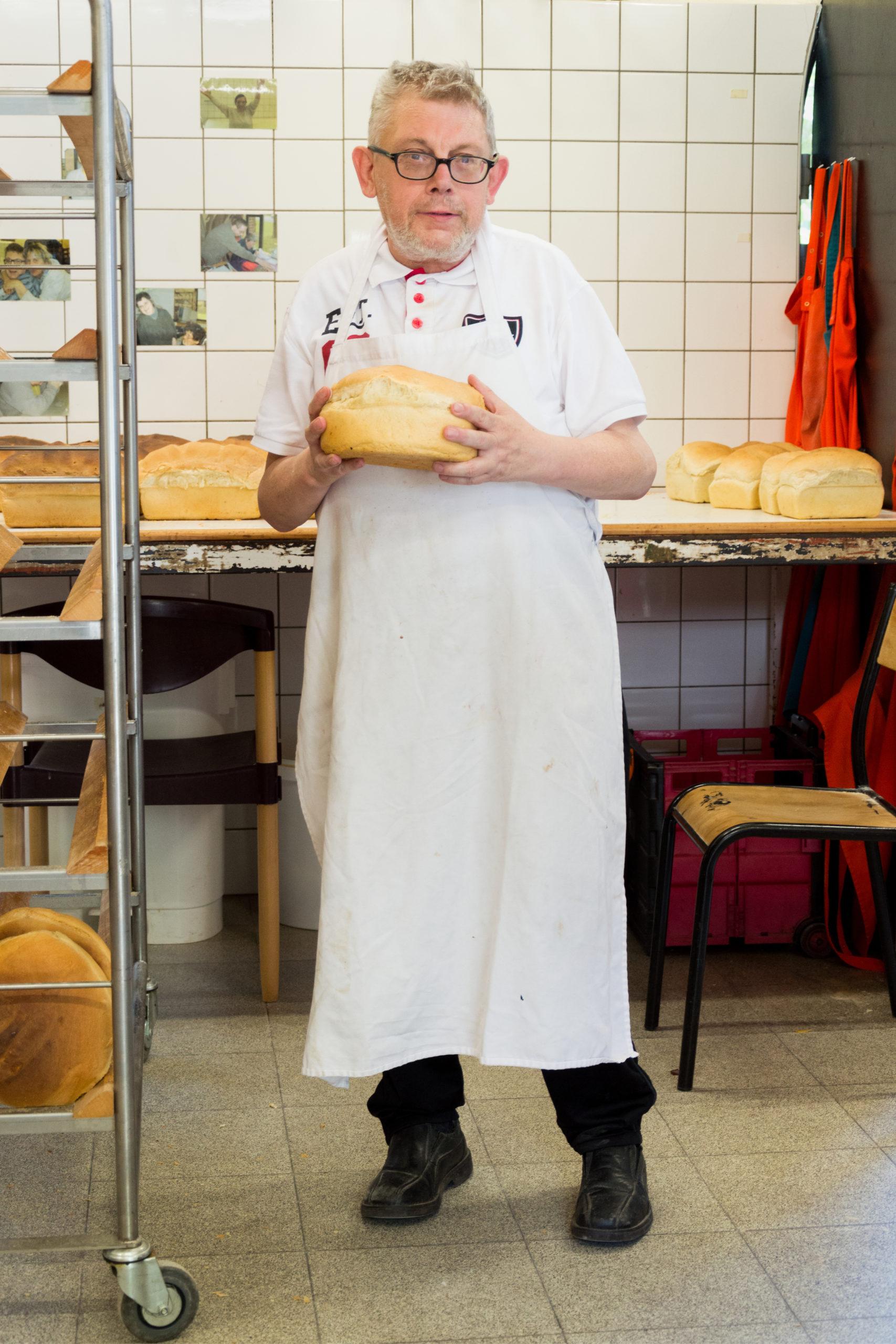 Homme handicapé dans une cuisine en habit de boulanger tenant en main un pain
