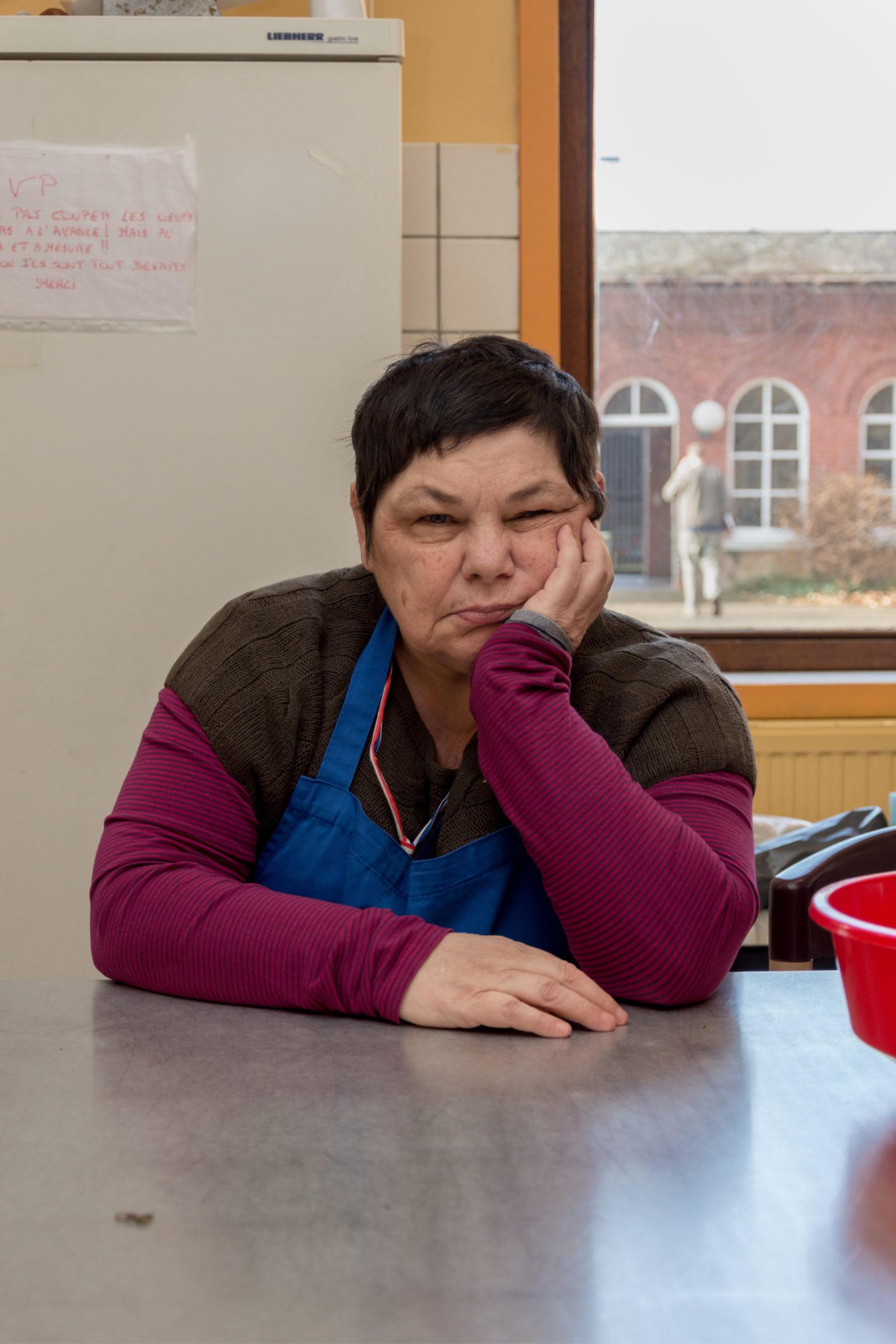 Dame handicapée dans une cuisine, assise à une table et tenant sa tête avec sa main gauche