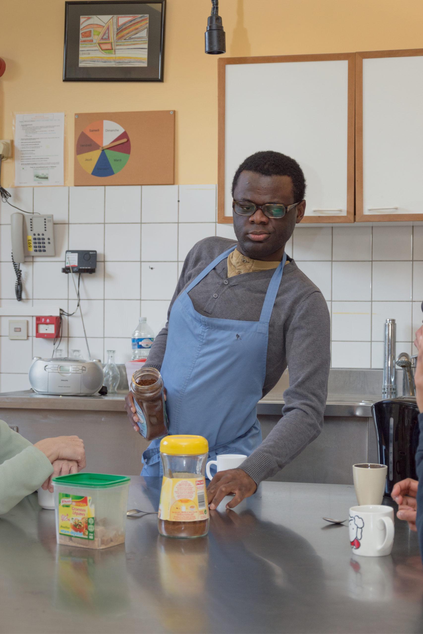 Homme noir handicapé dans une cuisine préparant un café