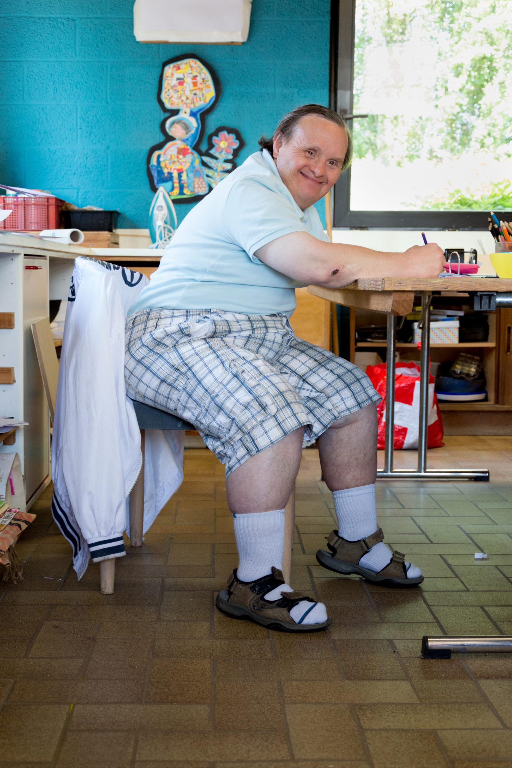 Homme handicapé souriant assis à une table d'école en train d'écrire et son regard dans notre direction